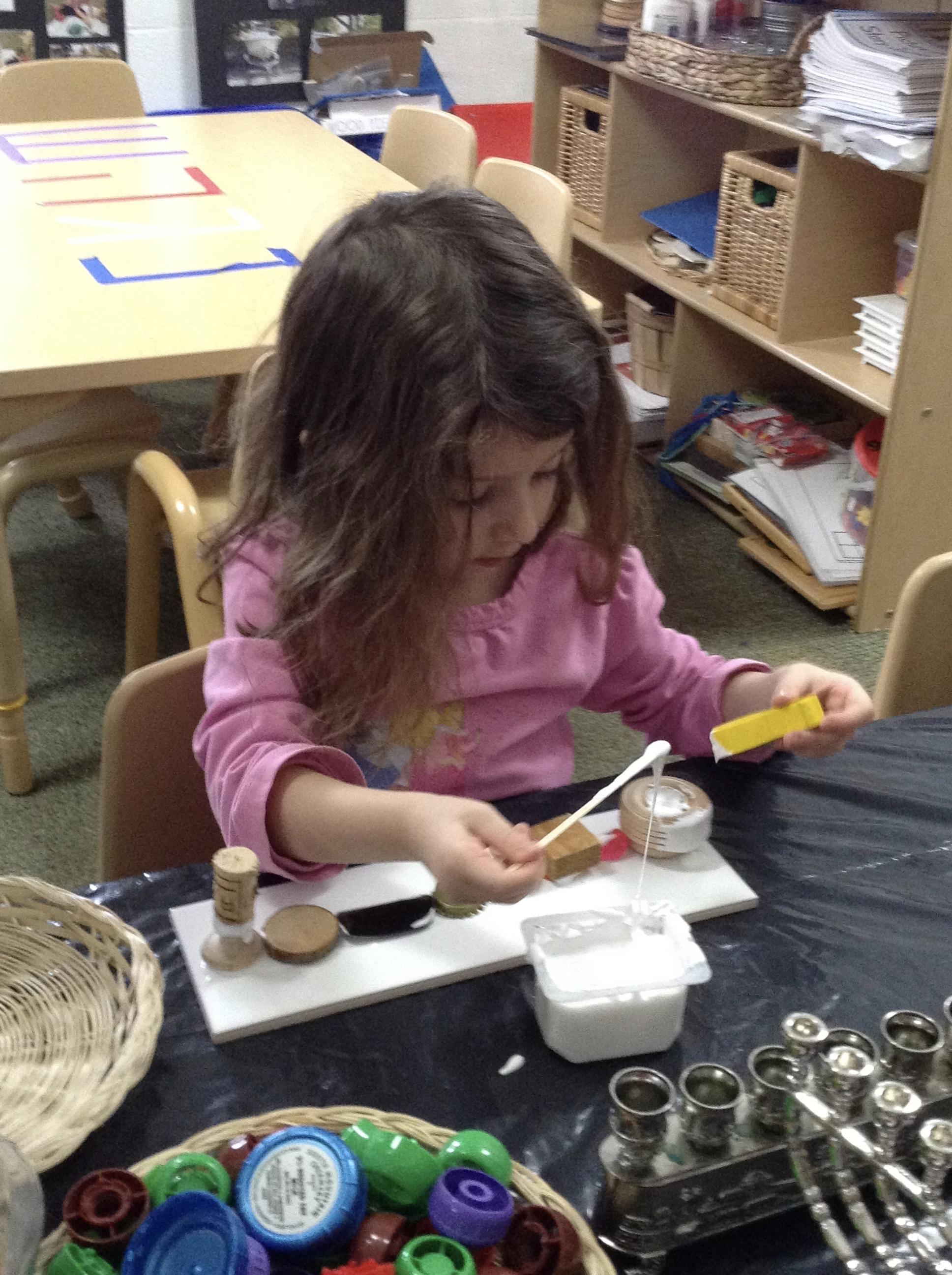 Creating a chanukiah using loose parts. (Pre-K)